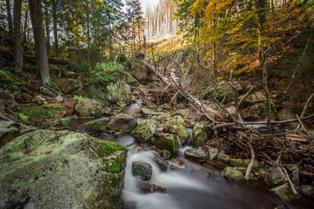 Mountain stream with waterfall in an autumn forest. time exposure