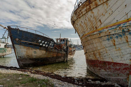 rotting ships with peeling paint and rotten structures on the Cemetery boat in Brittany, France