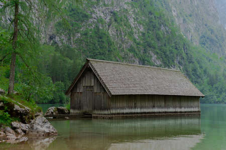 A boathouse on a blue mountain lake with high mountains in the background Archivio Fotografico