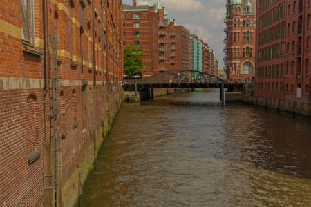 a river through hamburg with big red houses and in the background a bridge