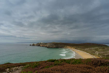 a colorful coastal area with rocks and dark rain clouds