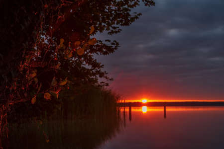Sunrise - Sunset over a lake with a blurred background and green leaves
