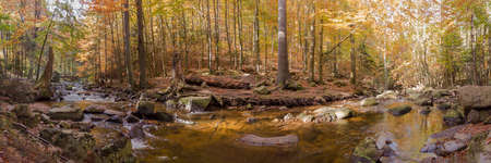 A river in the mountains with stones in autumn as a panorama Stock fotó