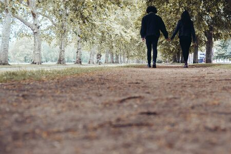 Couple holding hands in the park during the day