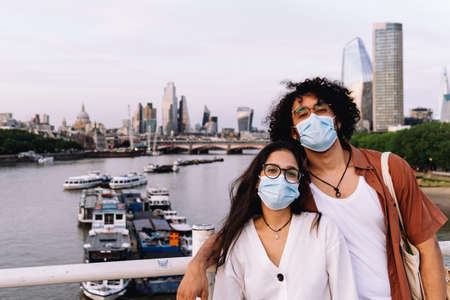 Happy couple traveling with new safety measures wearing protective face mask. Skyscrapers behind them