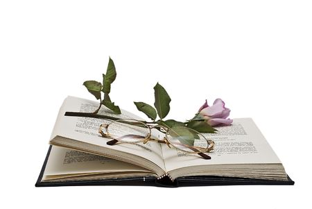 Rose and glasses on an open book. photo