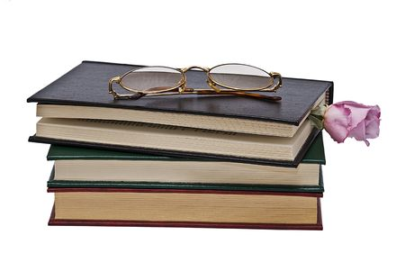 Glasses and rose on three books. photo