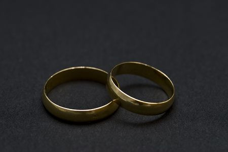 Two golden rings on a black background. photo