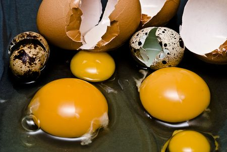Cracked hen and quail eggs. photo