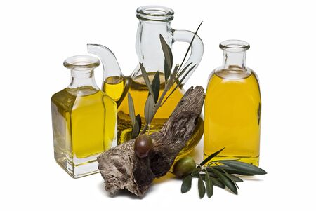 oil mill: Some olive oil bottles and olives on its branch.