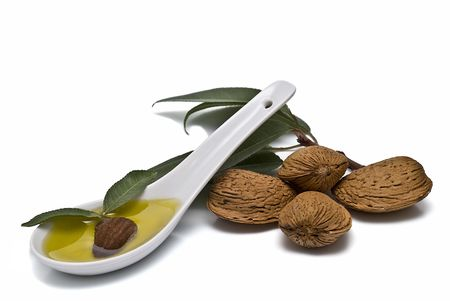 A spoon full of almond oil and some almonds.