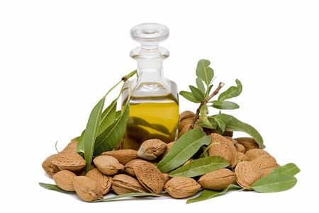 A bottle of almond oil and some almonds. photo