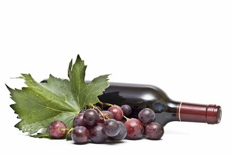 A bottle of wine and some grapes. photo