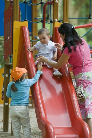 recreational area: Children enjoying the playground with their mother. Stock Photo
