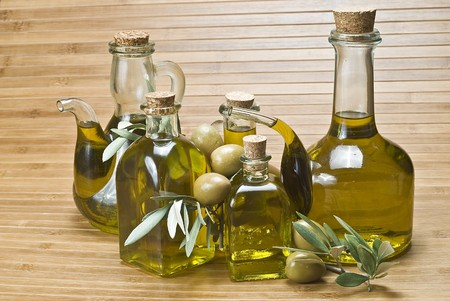 Some bottles of olive oil and some olives on a bamboo mat. photo