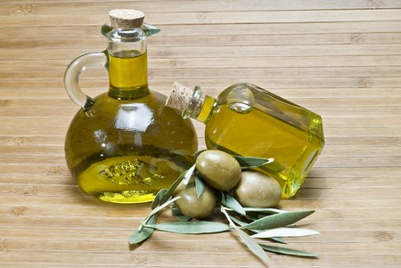 Two bottles of olive oil and some olives on a bamboo mat. Stock Photo