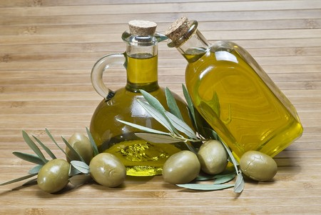 Two bottles of olive oil and some olives on a bamboo mat. photo