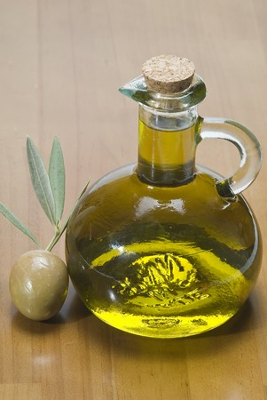 A cruet with olive oil and one barrancabermeja olive. photo