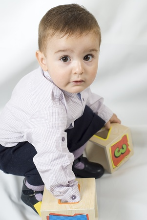 A child paying with wooden boxes. photo