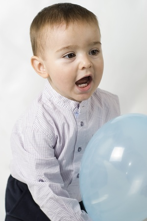 A beautiful baby with a blue balloon. photo