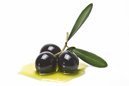 Black olives on some olive oil isolated on a white background.