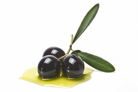 hoja de olivo: Aceitunas negras sobre aceite de oliva aislado en un fondo blanco. Foto de archivo