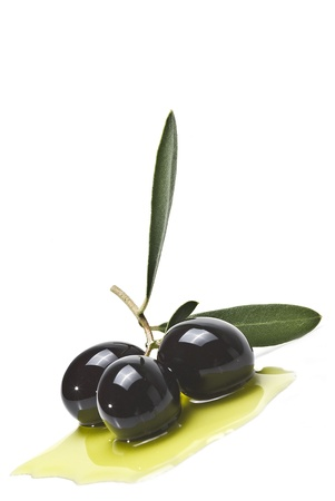 culinary: Black olives on some olive oil isolated on a white background.
