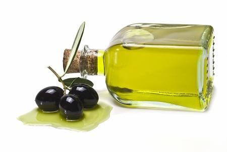 Una botella de aceite de oliva y algunas aceitunas negras aisladas sobre fondo de ablancos.