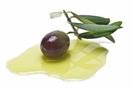One olive on its branch with some olive oil isolated on a white background.