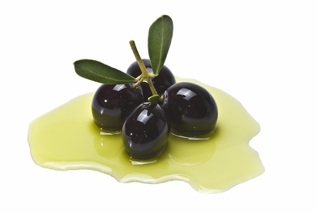 foglie ulivo: Some black olives on some olive oil isolated on a white background.