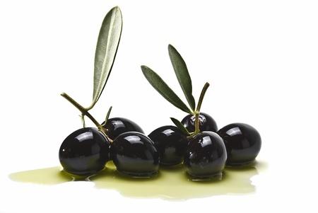 白い背景上に分離されていくつかのオリーブ オイルにいくつかの黒オリーブ。