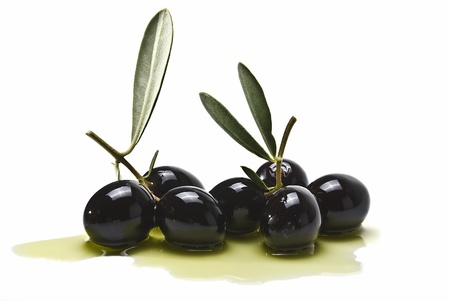 Some black olives on some olive oil isolated on a white background.