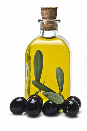 extra virgin olive oil: A bottle of olive oil and some black olives isolated on awhite background. Stock Photo