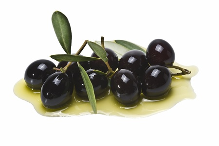 Some black olives on some olive oil isolated on a white background. photo