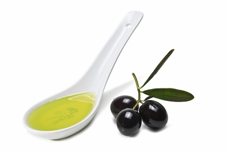 A spoon with olive oil and some black olives isolated on a white background. photo