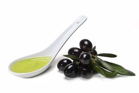 A spoon with olive oil and some black olives isolated on a white background.