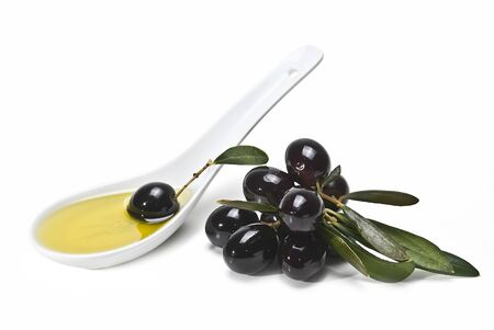 A spoon with olive oil and some black olives isolated on a white background. Stock Photo - 8759330