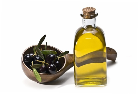 extra virgin olive oil: A bottle of olive oil and some olives in a big spoon.