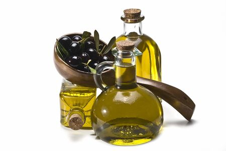 Some bottles of olive oil and some black olives in a big spoon. Stock Photo - 8759432