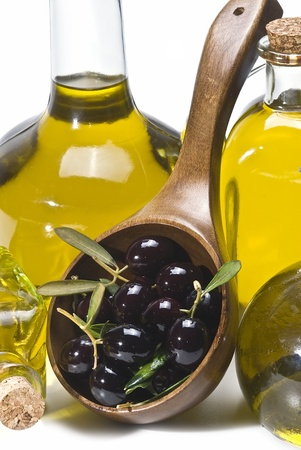 Some black olives in a spoon and some bottle of oil. Stock Photo - 8759438