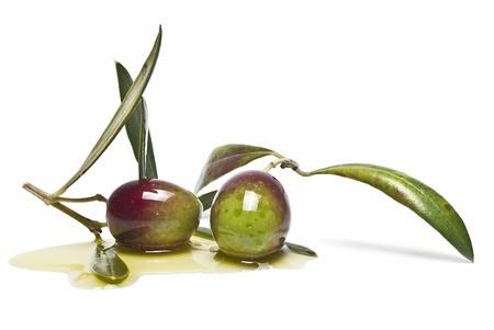 Twee groene olijven op wat olijf olie geïsoleerd op een witte achtergrond.