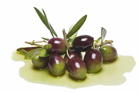Some olives with leaves on some olive oil isolated on a white background.