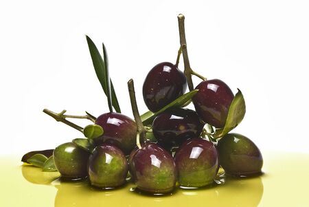 Some olives on olive oil on a white background. Stock Photo