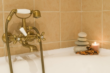 Detail of a bathtub faucet and some stones in zen balance. Stock Photo - 9159165