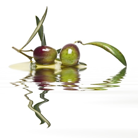 A pair of green olives reflected on olive oil.