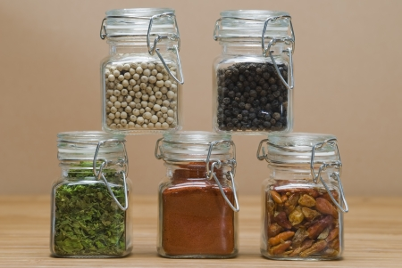 Some jars with spices on a wooden surface.