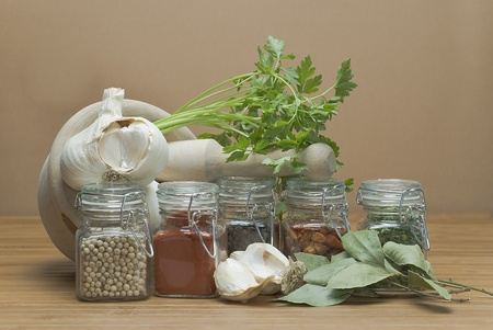 Some jars with spices on a wooden surface. photo
