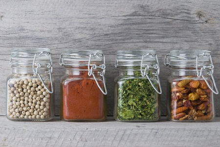 Some jars with spices on an old spice rack. photo