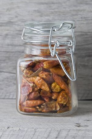 A jar with chilli on an old wooden surface. photo