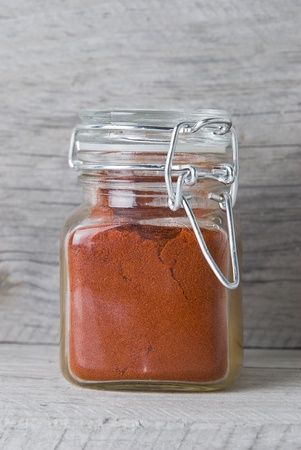 A jar with paprika on an old wooden surface. photo